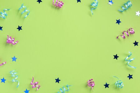 Colorful serpentine and stars, on green  background. Celebration concept .Flat lay, top view, copy space. 版權商用圖片
