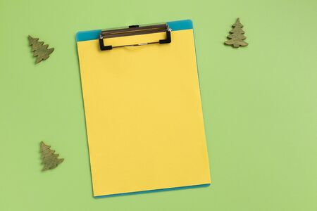 Clipboard with yellow sheet and christmas trees, on green background. Flat lay, top view, copy space.