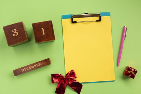 Christmas or New Year planning concept. Clipboard, wooden calendar,  pen, on green background. Flat lay, top view, copy space.