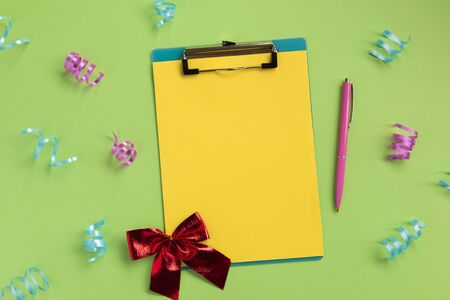 Celebration planning concept. Clipboard, pen, bow, serpentine, on green background. Flat lay, top view, copy space.