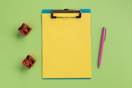 Christmas or New Year planning concept. Clipboard with yellow sheet and pen, on green background. Flat lay, top view, copy space.