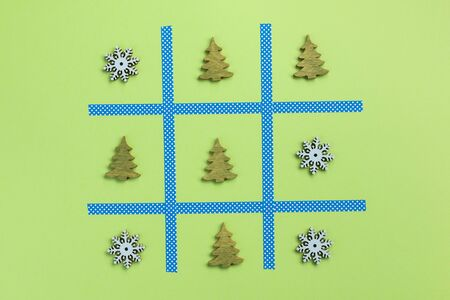 Tic tac toe game with christmas toys, isolated on green background. Christmas, winter concept. Flat lay, top view. Stok Fotoğraf
