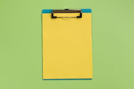 Clipboard with yellow sheet, on green background. Flat lay, top view, copy space.