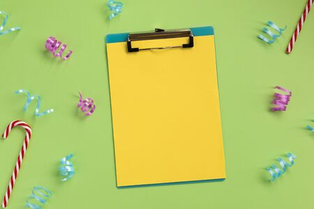 Celebration planning concept. Clipboard and serpentine, on green background. Flat lay, top view, copy space. Banque d'images