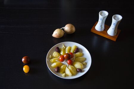 Boiled potatoes islolated with organic black olives, onion and small tomatoes 版權商用圖片