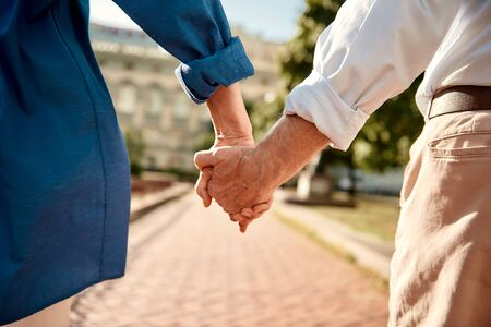 You and me forever. Close-up of elderly couple holding hands while walking together outdoors. Family. Love concept Stok Fotoğraf