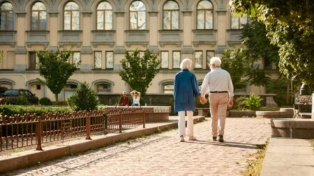 Come with me. Back view of elderly couple holding hands while walking together outdoors. Family. Love concept Standard-Bild