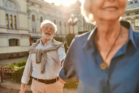 Time doesnt matter love is forever. Beautiful and happy elderly couple holding hands and smiling while spending time together outdoors Stock Photo
