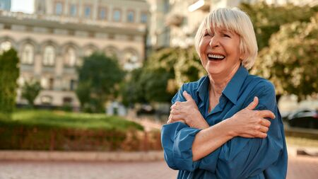 I am optimist. Beautiful senior woman in casual wear hugging her shoulders and smiling while standing outdoors on a sunny day. Old age. Happiness