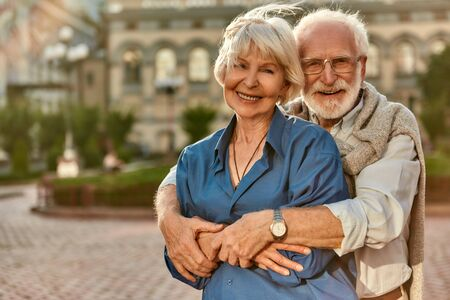 Love has no age limit. Happy senior couple in casual clothing embracing each other and smiling while standing outdoors. Love concept. Family