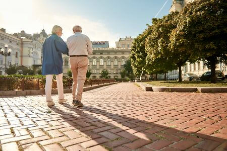 What a beautiful day! Back view of elderly stylish couple walking together outdoors. Family. Love concept