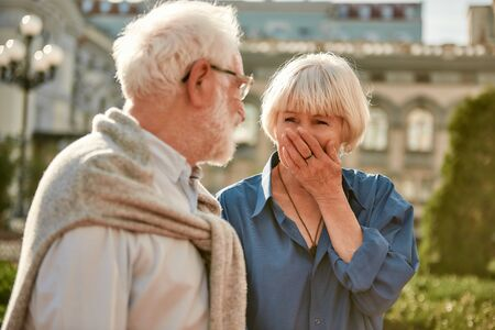 I love your sense of humor. Beautiful senior woman laughing and looking at her husband while standing together outdoors. Family. Love concept