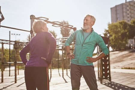 Senior people and gymnastics. Active happy mature family couple in sportswear doing morning exercises together, warming up while standing at the stadium