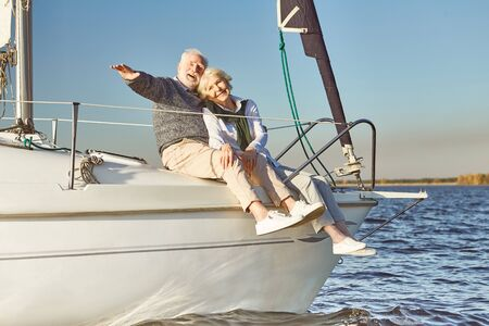 Anchors away. Happy senior couple hugging on sail boat or yacht deck floating in sea. Man hugging his woman while enjoying the view