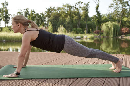 Full length of a fitness woman in sportswear doing plank exercise on a mat against amazing lake with green trees on the background on a sunny morning