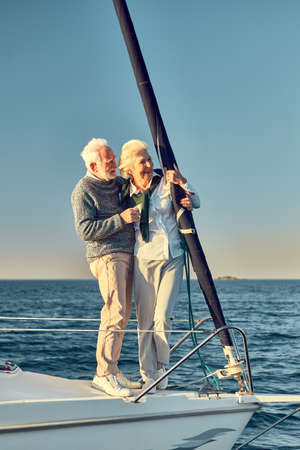 Full leghth of beautiful happy senior couple in love, retired man and woman standing on the side of sail boat floating in sea, hugging and enjoying view Foto de archivo