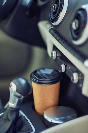 Drinking coffee in car. Vertical shot of a paper cup of coffee in the cup holder between seats