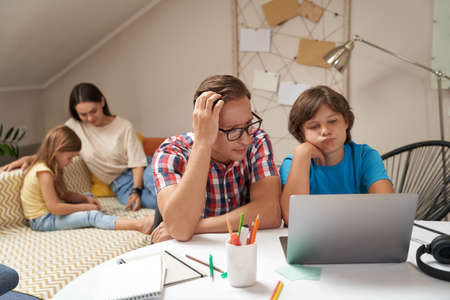 Worried father helping his little son with homework while mother and daughter sitting on sofa and playing with pazzles