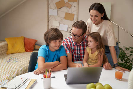 Young happy family working on laptop together, parents helping children with homework or studying online at home during covid 19 quarantine Stock fotó