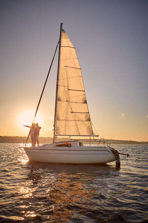 Vertical shot of a romantic senior couple enjoying enjoying amazing sunset sunset while standing on the side of sail boat or yacht deck floating in the sea