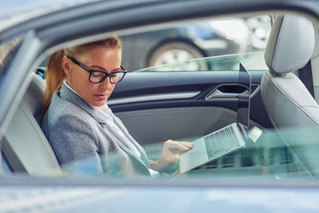 Working on the way to business meeting. Side view of a busy middle aged businesswoman using laptop while sitting on back seat in the car