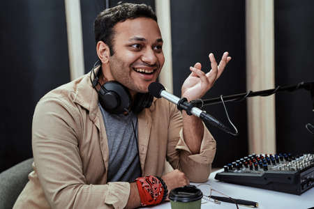Portrait of happy young male radio host smiling while speaking in microphone, moderating a live show Stock Photo
