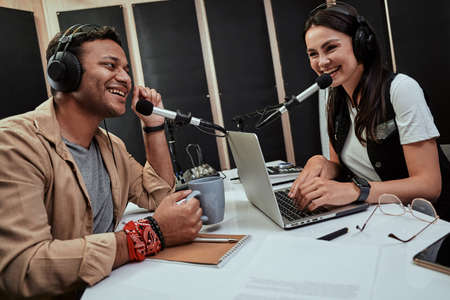 Portait of two happy radio hosts, young man and woman talking with each other while moderating a live show in studio Stock Photo