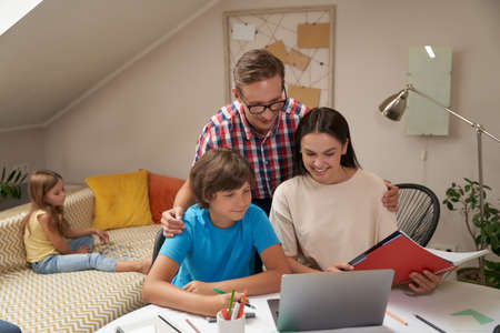 Homeschooling. Young positive parents helping his son with homework while his little sister sitting on sofa on the background and playing with puzzles