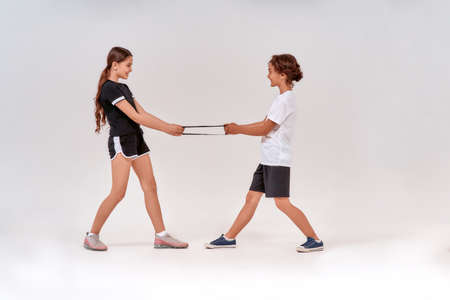 Full-length shot of happy teenage boy and girl having fun while exercising with resistance band, standing isolated over grey background Foto de archivo