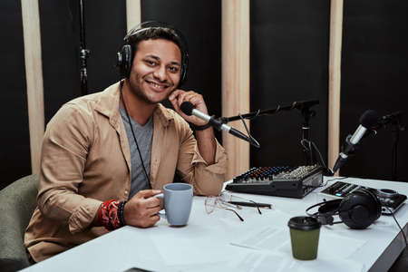Portrait of happy young male radio host having a drink, smiling at camera while moderating a live show Stock Photo