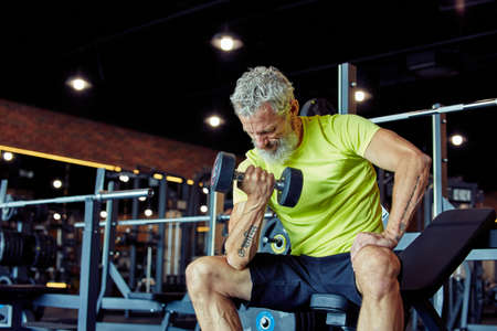 Getting strong arms. Focused mature man in sportswear lifting heavy dumbbells and pumping his biceps while working out at gym Stock Photo