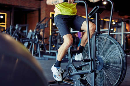 Cropped shot of athletic man in sportswear doing cycling on exercise bikes at gym, cardio workout