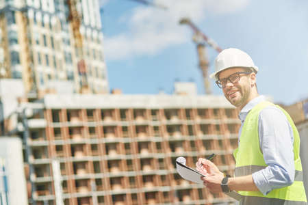 Young civil engineer or construction supervisor wearing helmet smiling at camera while inspecting building site and making some notes