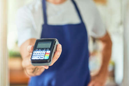 Paying terminal in businessman hand