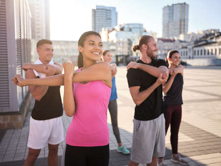 Team of happy young athletes doing hand stretching