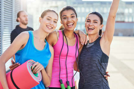 Happy young mixed race girls holding sport equipment Stockfoto