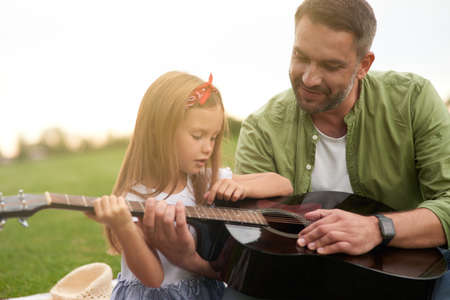 Portrait of curious little girl sitting with her loving father on a green grass in park and learning how to play guitar