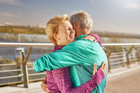 Happy together. Active mature family couple in sportswear embracing after having workout in the city park on a sunny morning. Joyful senior couple standing together outdoors
