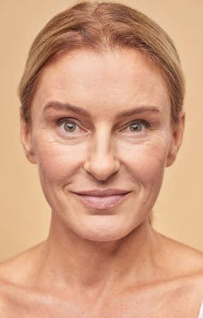 Smiling mature woman posing at camera in studio Stock Photo