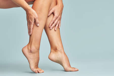 Cropped shot of a woman touching her legs with smooth, silky and soft skin after making a depilation, sitting over blue background