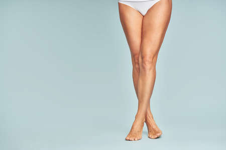 Perfect hair removal. Cropped shot of a woman with perfectly shaven legs standing over blue background