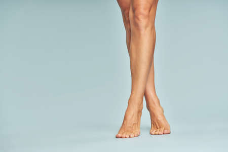 Depilation concept. Cropped shot of beautiful female legs with soft silky skin over blue background