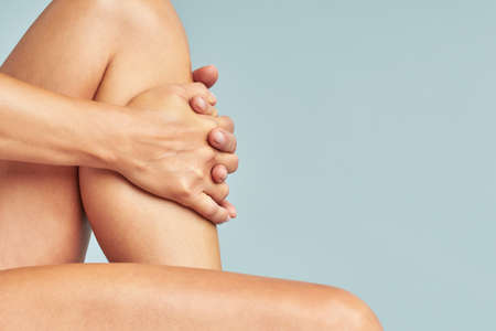 Cropped shot of a woman touching her soft and silky skin on legs after epilation while sitting over blue background