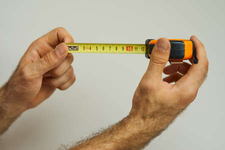 Hand of repairman holding a tape measure over white background