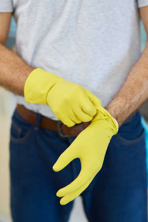 Get started. Close up shot of hands of man, professional male cleaner wearing gloves while getting ready for doing housework