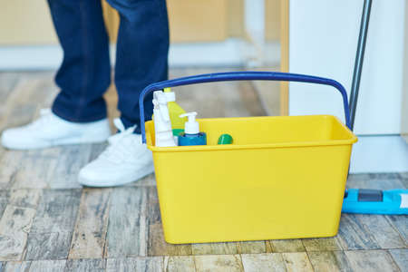 Close up shot of plastic bucket with detergents. Man getting ready for doing housework, cleaning floor indoors