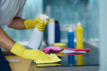 Neat Cleaning. Close up shot of hands of man, professional male cleaner wearing gloves, using spray detergent while cleaning oven in the kitchen