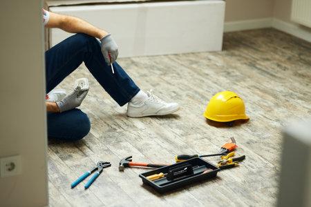 Home repairs. Cropped shot of handyman holding screwdriver and wall plug socket. Home repair hand tools on laminate flooring. Home improvement 免版税图像