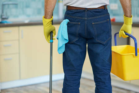 Cleaning guru. Cropped shot of professional male cleaner wearing gloves, holding plastic bucket and mop while getting ready for cleaning floor in the kitchen