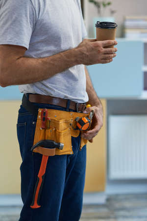 Coffee break. Cropped shot of professional repairman wearing a tool belt taking a break, drinking coffee while standing indoors